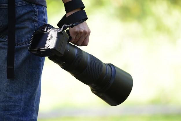 Fotografo che tiene una macchina fotografica in un'atmosfera rinfrescante al mattino