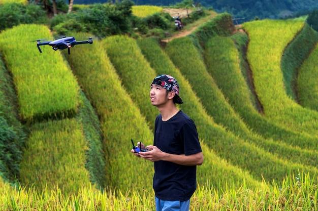 Fotografo con drone i campi di riso su terrazzamenti del distretto di mu cang chai, provincia di yenbai, a nord