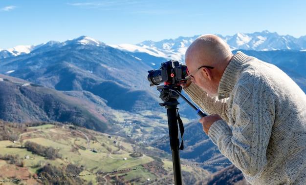 Fotografo con fotocamera digitale in cima alla montagna