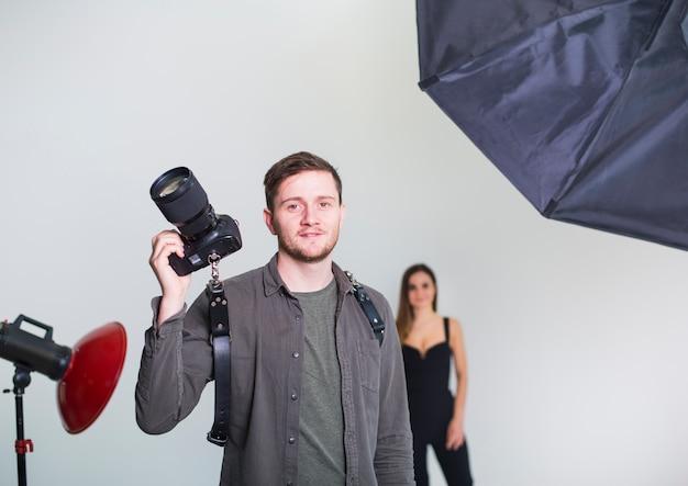 Fotografo con fotocamera in piedi in studio