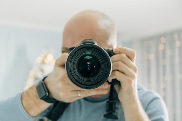 Fotografo con la macchina fotografica a disposizione guardando attraverso l'obiettivo