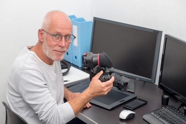 Fotografo con la macchina fotografica all'ufficio con il computer
