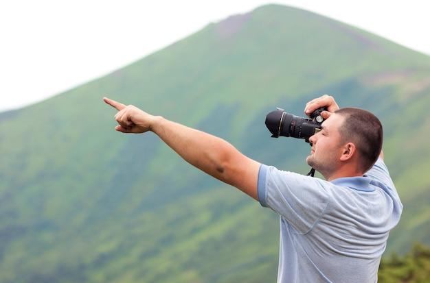 Fotografo con una macchina fotografica che prende immagine delle montagne che indicano con il dito