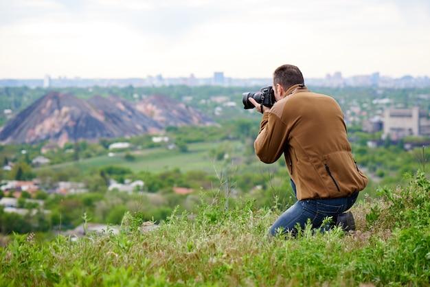 Fotografo con una macchina fotografica dslr su una collina