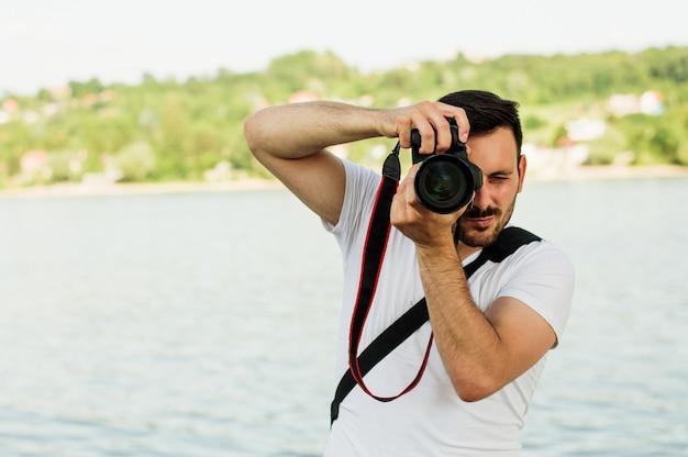 Fotografo del giovane che prende le immagini con il suo dslr