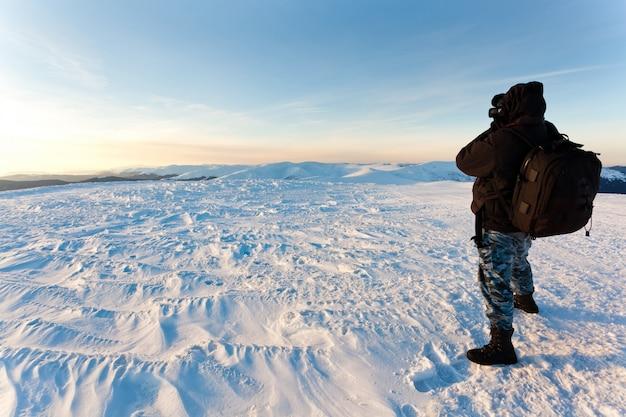 Fotografo del giovane nell'abbigliamento di inverno che sta e che fa foto al sole