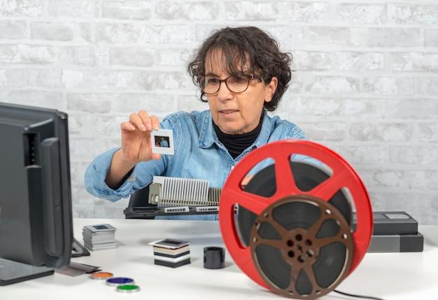 Fotografo della donna che esamina la diapositiva del film