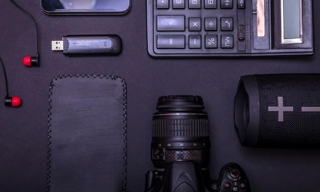 Fotografo dello spazio di lavoro di vista superiore con la macchina fotografica digitale, il calcolatore, l'unità usb e l'accessorio sul fondo nero della tavola con lo spazio della copia.
