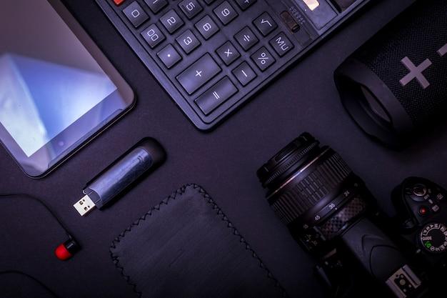 Fotografo dello spazio di lavoro di vista superiore con la macchina fotografica digitale, il calcolatore, l'unità usb e l'accessorio sul fondo nero della tavola