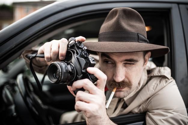 Fotografo di paparazzo che utilizza la macchina fotografica nella sua auto