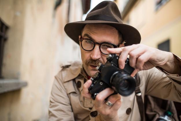 Fotografo di paparazzo o spia, uomo che utilizza la macchina fotografica in una strada cittadina