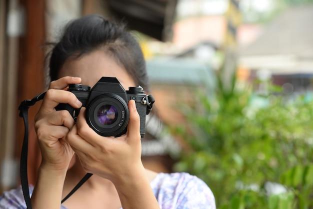 Fotografo di signora in vestito d'annata che tiene la retro macchina da presa in sua mano