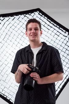 Fotografo di smiley con vista bassa e ombrello fotografico