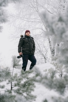 Fotografo di viaggiatori che scatta foto nella foresta invernale