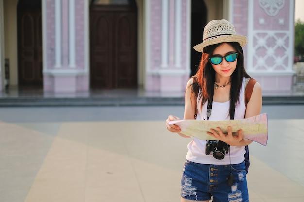 Fotografo donna che cammina nel vecchio mercato e utilizza la mappa locale.