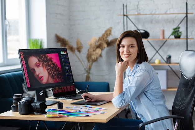 Fotografo e graphic designer che lavorano in ufficio con laptop, monitor, tavoletta grafica e tavolozza di colori.