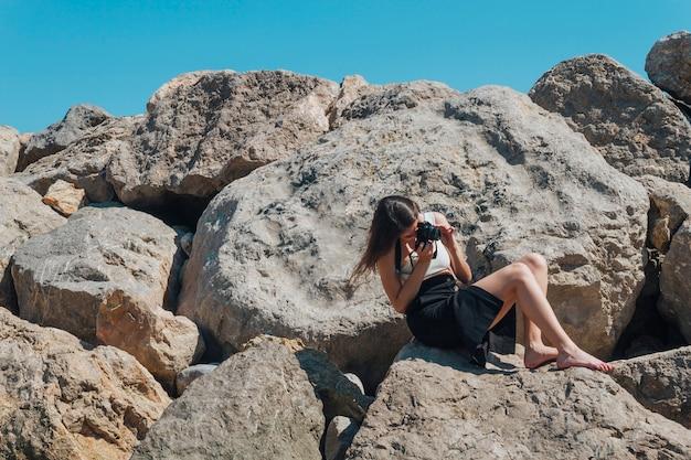 Fotografo femminile che si siede sulla roccia che prende foto con la macchina fotografica vicino al mare