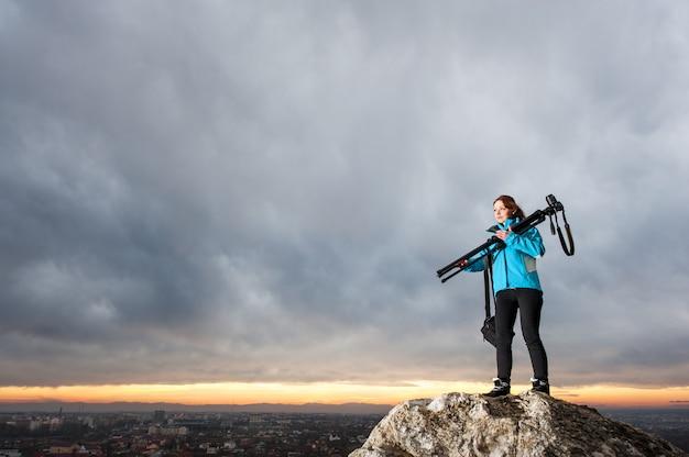 Fotografo femminile con la macchina fotografica sul treppiede sulla grande roccia