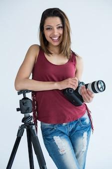 Fotografo femminile felice che sta nello studio