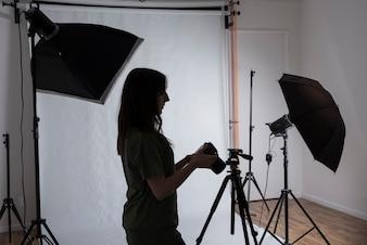 Fotografo femminile in studio fotografico moderno con attrezzature professionali