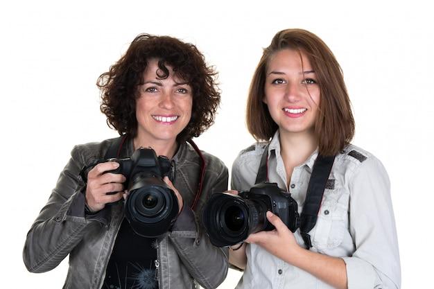 Fotografo femminile sorridente con due macchine fotografiche professionali isolate