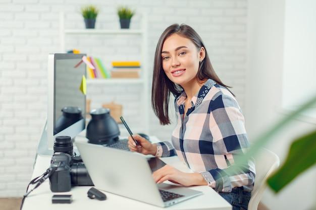 Fotografo grazioso della giovane donna con la macchina fotografica in ufficio
