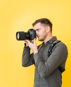 Fotografo maschio che cattura maschera con la macchina fotografica