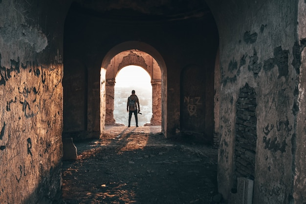 Fotografo maschio che sta nell'arco di vecchia architettura abbandonata