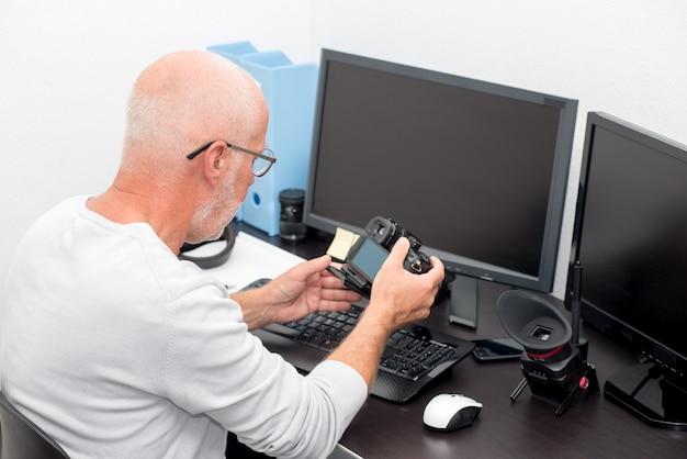 Fotografo maturo con la macchina fotografica all'ufficio con il computer