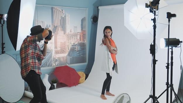 Fotografo professionista che chiede al modello di cambiare le pose mentre fa un servizio fotografico in studio