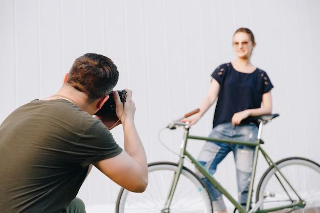 Fotografo professionista che fa un servizio fotografico di giovane donna alla moda che si siede sulla bici e che posa alla macchina fotografica, contro la parete bianca. all'aperto.