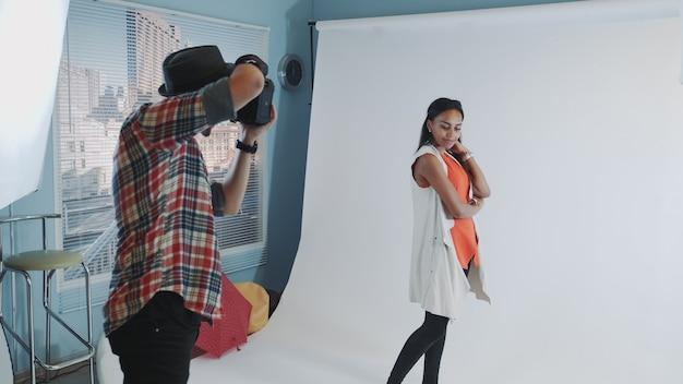 Fotografo professionista che lavora in studio scattando foto di una modella nera