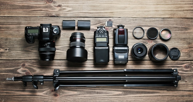 Fotografo professionista dell'attrezzatura su una tavola di legno. fotocamera, obiettivi, flash, filtri luminosi, treppiede.