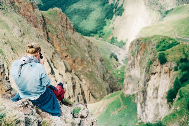 Fotografo seduto in alto in montagna.
