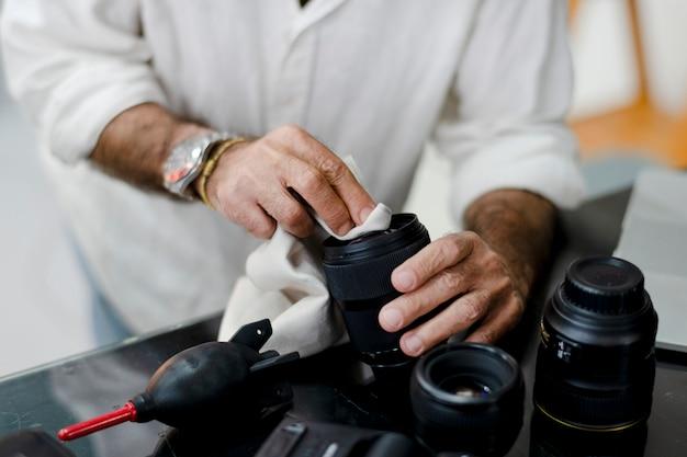 Fotografo senior che pulisce il suo obiettivo