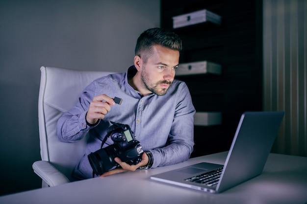 Fotografo serio che esamina computer portatile e che mette la scheda di memoria nella macchina fotografica mentre sedendosi a tarda notte nello studio.