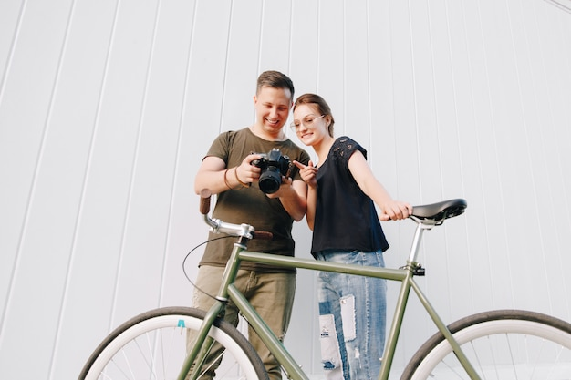 Fotografo sorridente e donna felice che controllano le foto dopo la fucilazione della foto, stante con la retro bici sopra la parete bianca. all'aperto.