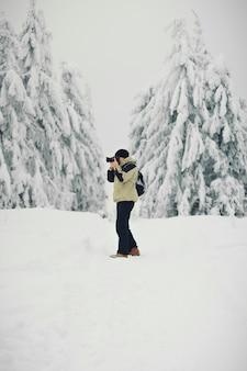 Fotografo sul lavoro tra gli alberi su una montagna innevata