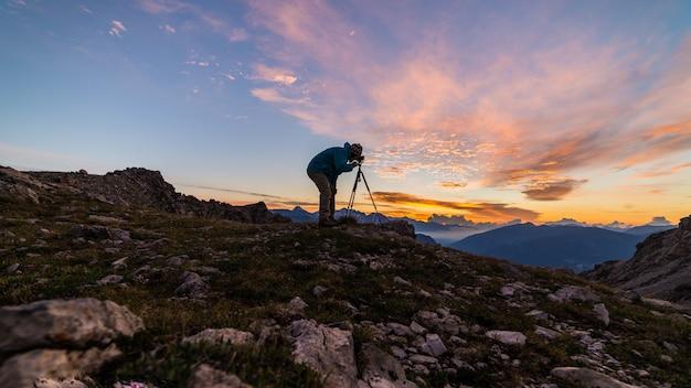 Fotografo sulla cima della montagna con la macchina fotografica sul treppiede al paesaggio variopinto leggero di scenis del cielo di alba.