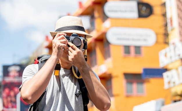 Fotografo turistico che cattura maschera in strada khao san bangkok, tailandia