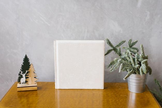 Fotolibro di matrimonio con copertina in pelle bianca circondata da un albero di natale in un secchio di metallo