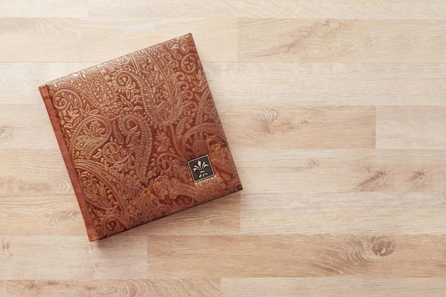 Fotolibro, quaderno o diario con copertina in vera pelle. colore marrone con stampa decorativa. album fotografico di matrimonio o di famiglia. copia spazio.