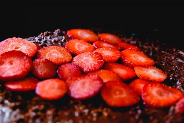 Fragola a fette tagliata su una torta su un vassoio prima di cuocerla, a forma di cuore.