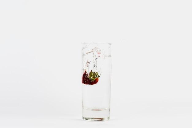 Fragola che cade nel bicchiere d'acqua