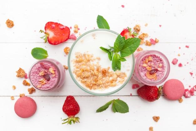 Fragola con yogurt su superficie di legno rustica bianca, dessert alla panna
