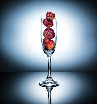 Fragola fresca nel bicchiere di champagne, stare sul pavimento riflettente