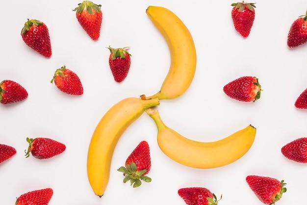 Fragola rossa luminosa e banana gialla su fondo bianco