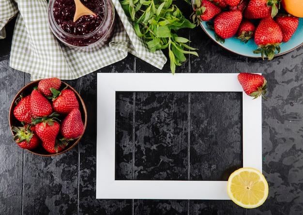Fragola vista dall'alto con marmellata di fragole alla menta e fetta di limone su sfondo nero