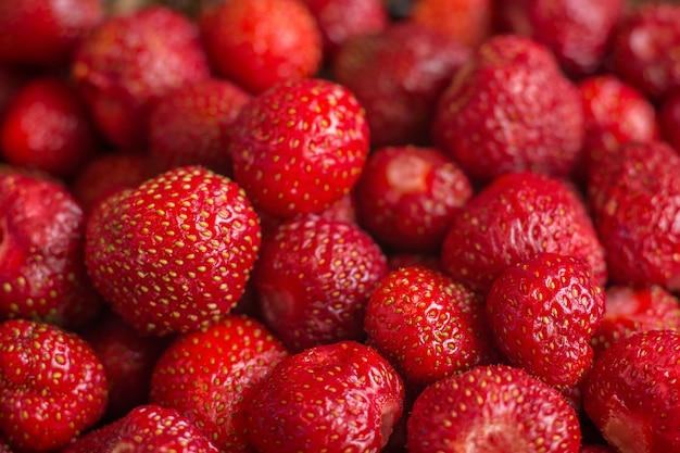 Fragole appena raccolte, full frame. bacche fresche dolci rosse come struttura.