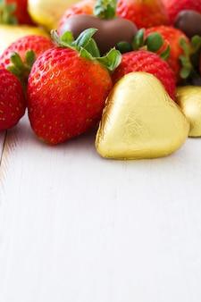 Fragole e bonbon del cioccolato sulla tavola di legno bianca